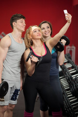 Group of athletes taking selfie with dumbbells in fitness center