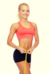 smiling sporty woman with measuring tape