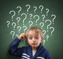 Child thinking with question mark on blackboard