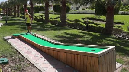 A boy plays in the mini golf