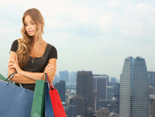 young woman with shopping bags over city