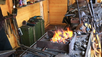 smith kindles coals in a smiths hearth