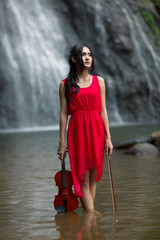 Young woman playing violin at waterfall