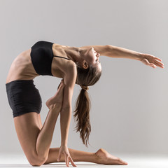 Yogi gymnast girl doing asana Ustrasana or Camel Pose
