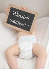 Baby hält Tafel mit Aufschrift Windelwechsel