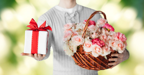 man holding basket full of flowers and gift box