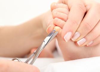 Mutter schneidet Baby die Zehennägel