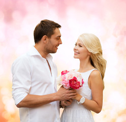 happy couple with flowers over lights background