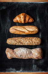Different kinds of bread rolls on black from above