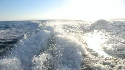 View of ocean from moving motor yacht with wake