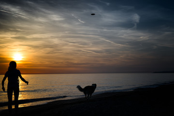 Girl with dog and frisbee to the sea