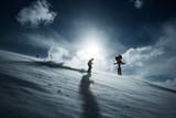 Skifahrer bei Gegenlicht vor Schneekanone