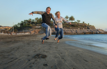 Man and woman jumping on the beach