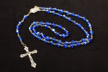 Blue glass beads rosary isolated on the dark background