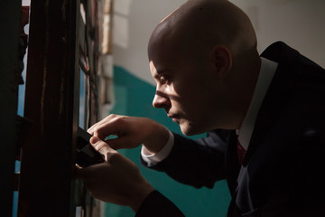 Bald hitman is going to open the door with the master keys.