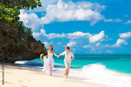 happy bride and groom having fun on a tropical beach - 76176368