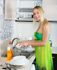 Happy  housewife in green washing dishes