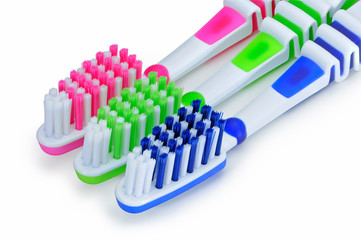 Blue, green, pink toothbrushes isolated on white background