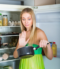 Woman holding foul food near fridge