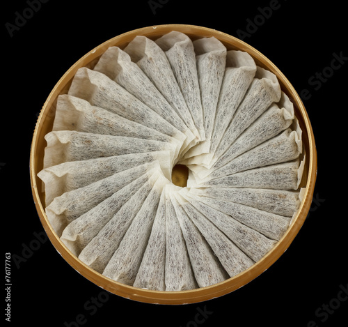 A bunch of swedish snus in a round container isolated on black