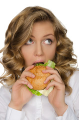 Young woman biting burger and looking away