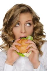 Young woman biting burger and looking away