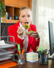 Hungry employee eating tasty salad