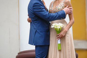 groom hugging woman at a wedding bouquet of white calla lilies