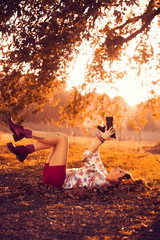 girl lying on grass at sunset and taking photo of tree
