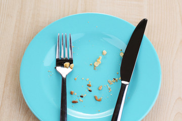 Plate with crumbs on wooden background
