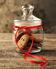 Cookies in a jar decorated with a red ribbon