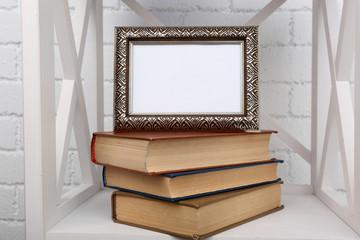 Photo frame with books on shelf, on