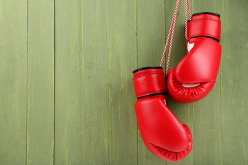 Pair of boxing gloves on color wooden background