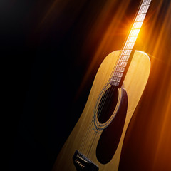 acoustic guitar on a black background in the rays of light