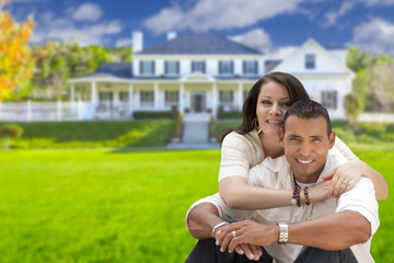 Happy Hispanic Young Couple in Front of Their New Home