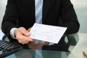 Midsection Of Businessman Showing Cheque
