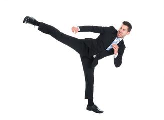 Businessman Kicking Over White Background