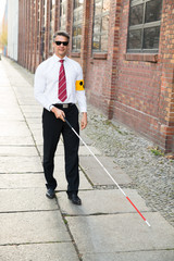 Blind Man Walking On Sidewalk Holding Stick