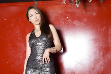 赤い壁の前に立つイブニングドレスの女性