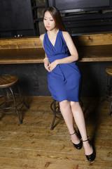 カウンターに座るカクテルドレスの女性