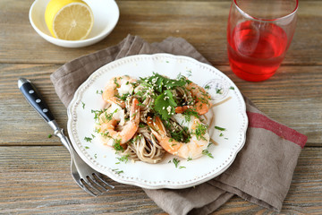 Buckwheat noodles with shrimp and cilantro on a white plate