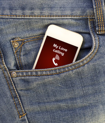 white mobile phone with call from my love in jeans pocket