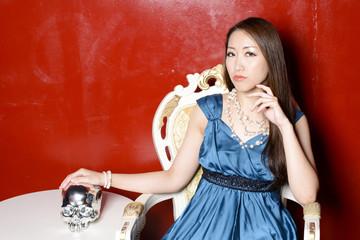 赤い壁の前に座ってドクロをなでるカクテルドレスの女性