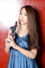 赤い壁の前に立って銃を持つカクテルドレスの女性