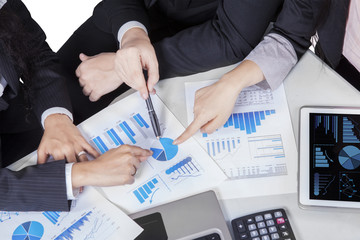 Business team hands pointing pie chart