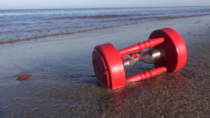 broken vintage red hourglass sandglass on sea beach