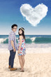 Couple with heart cloud at beach