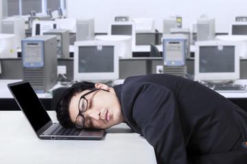 Entrepreneur in business suit sleeping in office