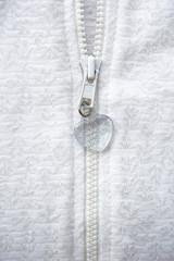 Zipper in heart shape on white fabric background