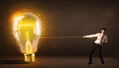 Business man pulling a big bright glowing light bulb